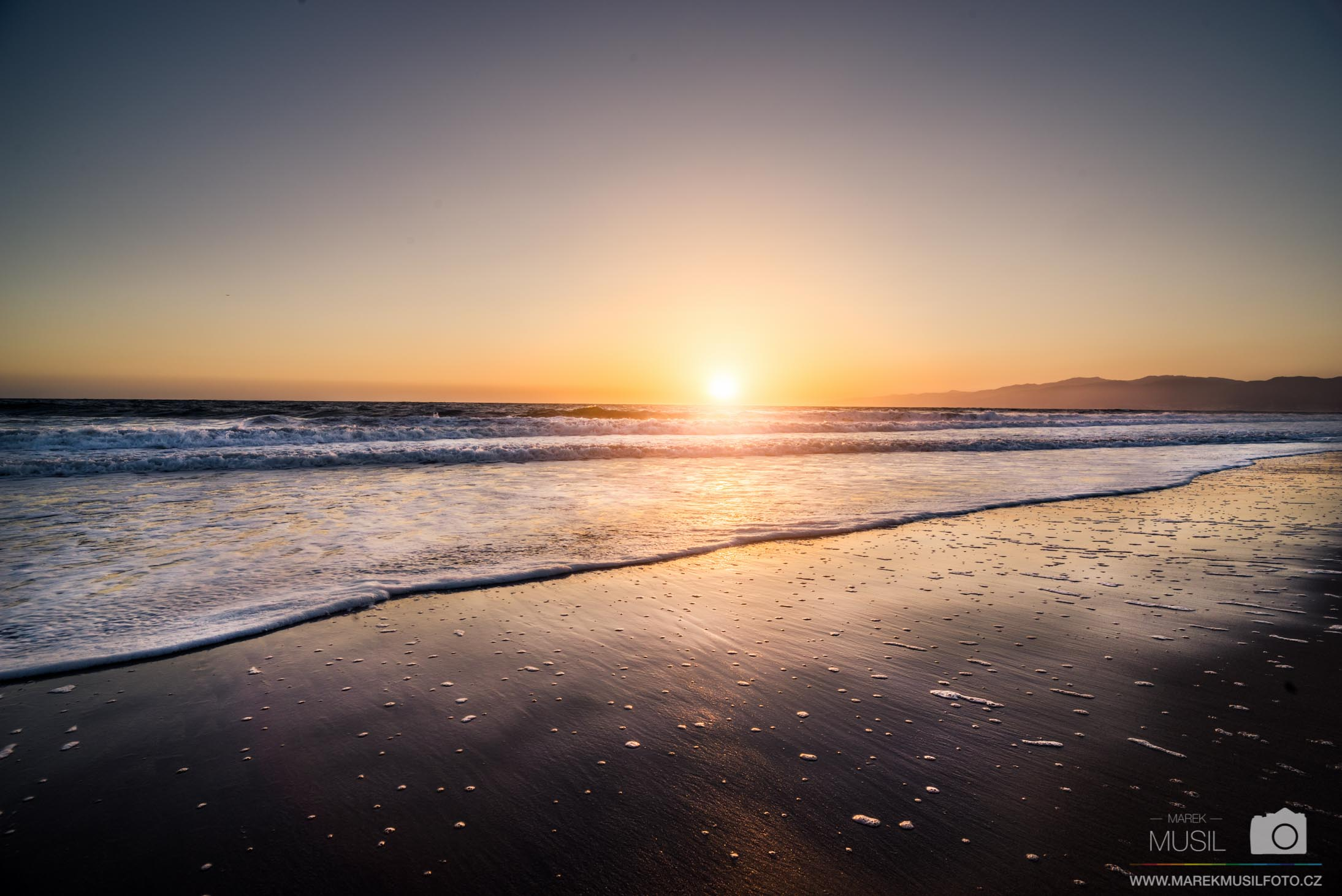 Západ slunce na pláži v Santa Monice.