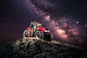 Fotografie traktoru Case IH s vánoční dekorací a mléčnou dráhou v pozadí.